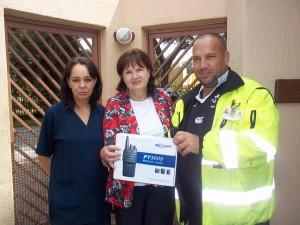 Annete Brand en Reinetta Ridley van La Reynette Centre ontvang die twee rigting radio van Martin Oosthuizen van Polisieringsforum KDP